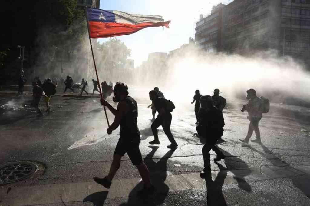 Miembros de carabineros dispersan a los manifestantes lanzando agua durante una nueva jornada de protestas en contra del gobierno del presidente de Chile, Sebastián Piñera, en Santiago (Chile). Crédito: EFE