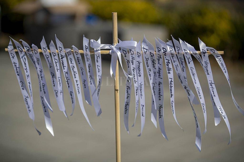 Listones con nombres de trabajadores médicos durante una ceremonia para develar una placa en honor al personal médico que murió tratando de salvar a víctimas de la pandemia de la enfermedad causada por el coronavirus, en el marco del Día del Médico en México. Crédito: Xinhua