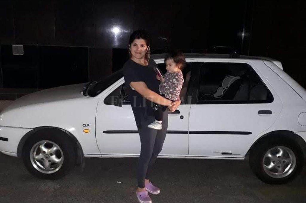 """Virginia, junto con su hijita, y el Ford Fiesta que fue """"levantado"""", a 50 metros de la Legislatura Provincial. Crédito: Gentileza"""