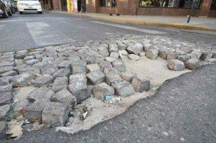 Fondo de Mantenimiento Vial: un tributo que se cobra, pero no se refleja   - San Martín esquina Corrientes. Un bache cubierto, en gran parte, por adoquines.   -