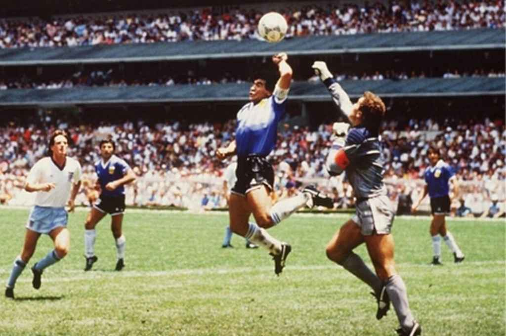 La mano de Dios. Diego ya la usó para llegar antes que Shilton. Fue el 1-0 a Inglaterra, después vendría el mejor gol de los mundiales y días después la usaría para levantar la copa. Sin dudas, el más grande futbolista de la historia.    Crédito: Archivo