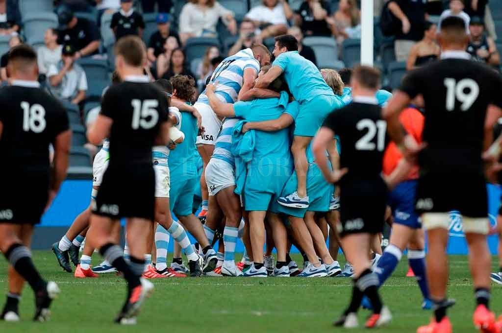 Síntesis adecuada de un hito histórico: Los Pumas celebran aunados en un abrazo interminable, mientras los All Blacks observan resignados. Fue el 14 de noviembre, en el Bankwest Stadium de Sydney. Crédito: Gentileza.