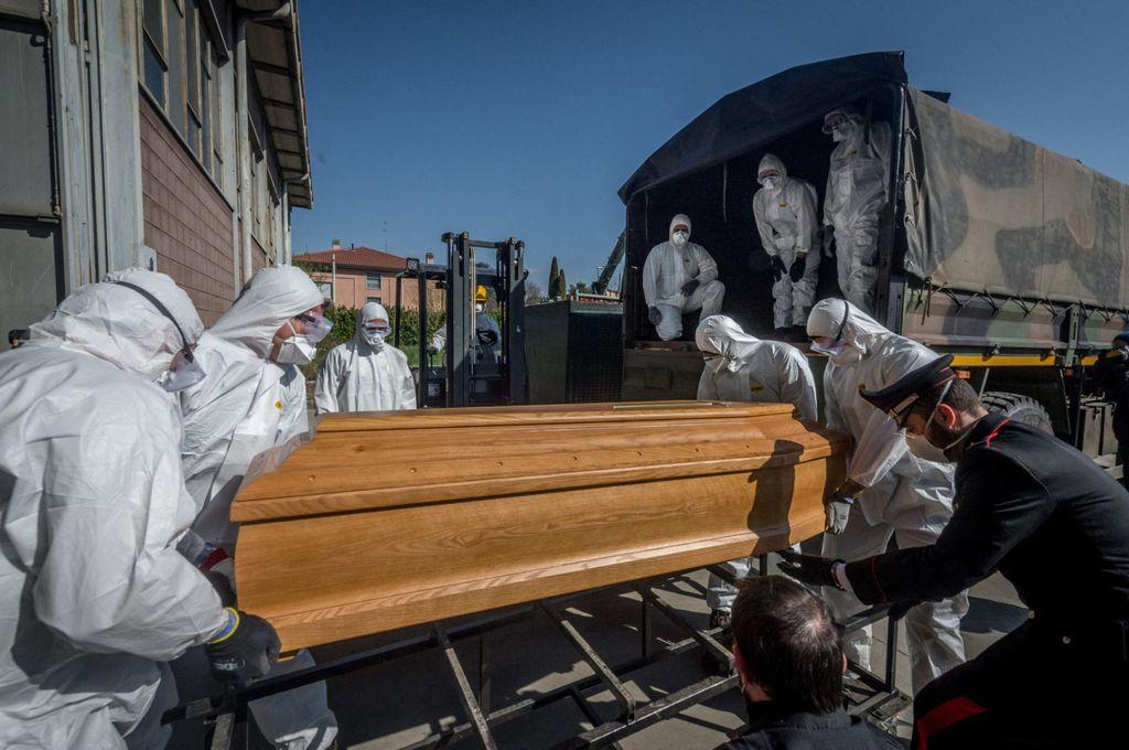 Personal militar y médico junto con carabineros transportan ataúdes desde un depósito en Ponte San Pietro, Italia. Crédito: Reuters