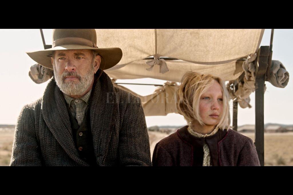 Tom Hanks encarna al capitán Jefferson Kidd, quien recorre el Oeste para leer noticias en los pueblos. Un día, su rutina se modifica cuando debe ayudar a una niña huérfana (Helena Zengel). Crédito: Universal Pictures, Netflix