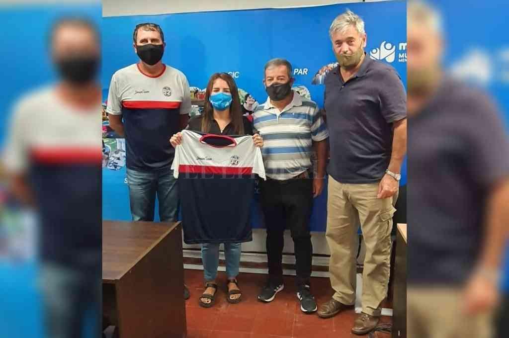 Yamila Cerezo recibió una remera de regalo de parte de Alejandro Comas y Darío Weglin. Acompaña Carlos Marini, colaborador de la organización. Crédito: Gentileza