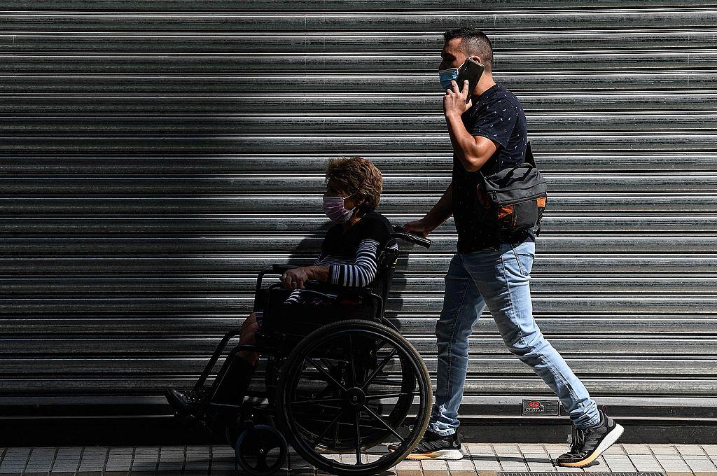 Un hombre traslada a una mujer en silla de ruedas por una calle, en Santiago, capital de Chile. Crédito: Xinhua/Jorge Villegas