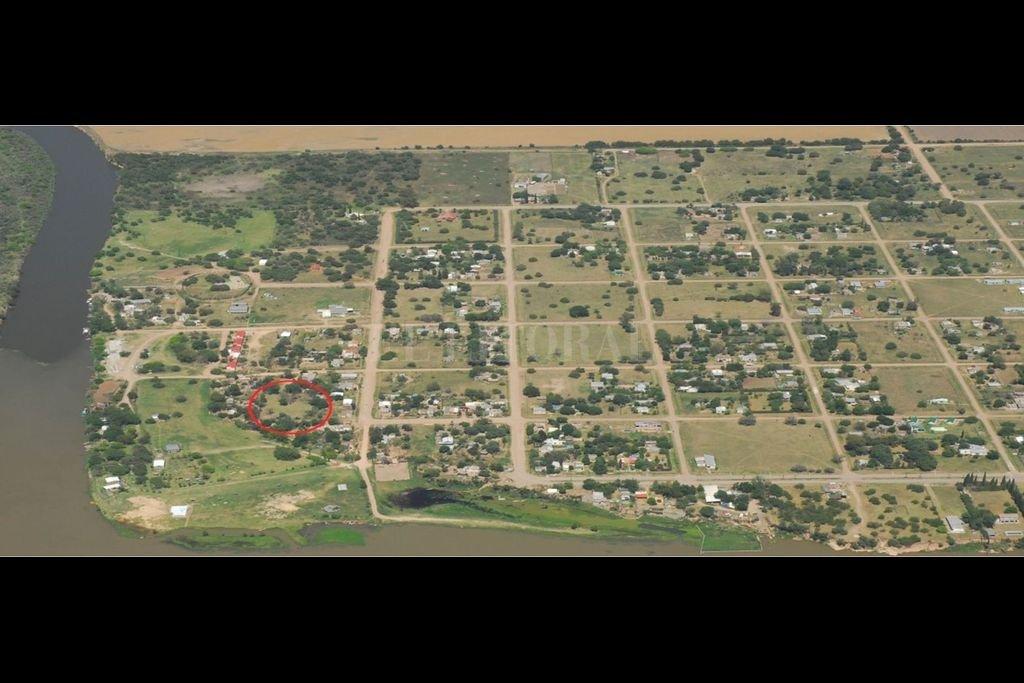 Vista aérea de la población de Puerto Gaboto donde se encuentra el sitio arqueológico (marcado con un círculo rojo). A la izquierda el río Carcarañá. Crédito: Comuna de Puerto Gaboto