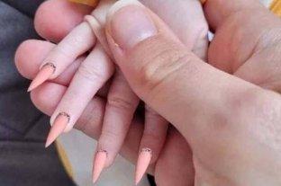 Una madre le pone uñas postizas y le hace una manicura a su bebé