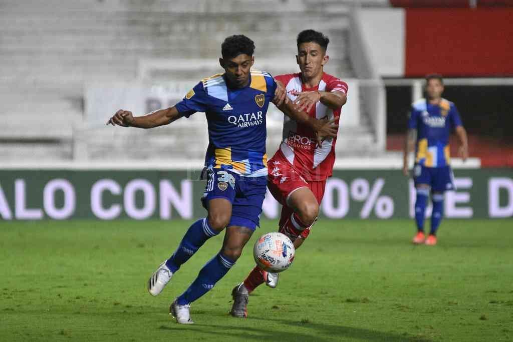 Cañete en acción en el partido ante Boca, corriendo en el mano a mano con Medina. El volante, con pasado