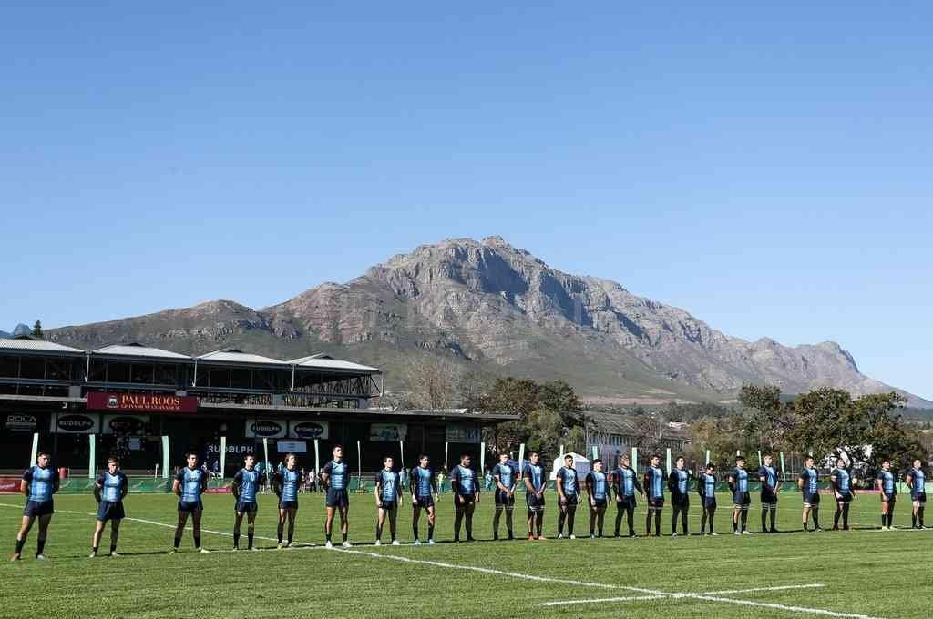 Paisaje sudafricano. El plantel argentino, durante la entonación del Himno Nacional, en la previa del partido disputado en Stellenbosch. Crédito: Gentileza UAR