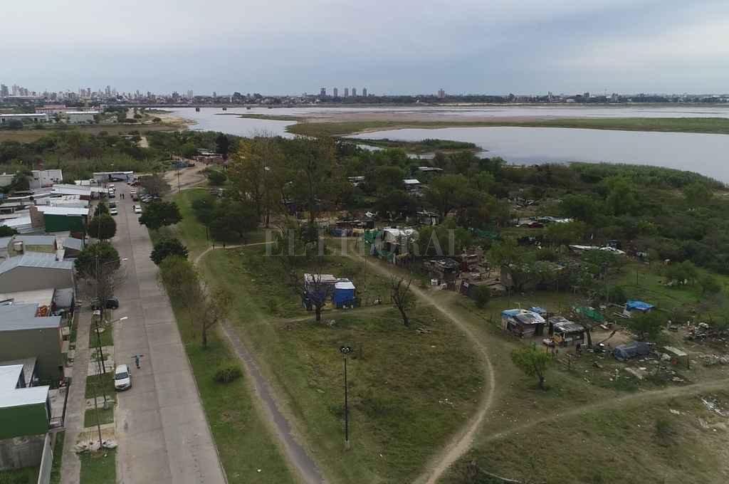 """Asentamiento en El Pozo: 57 familias y todo un barrio a la espera de una respuesta del Estado   - Contraste. A un lado de la imagen los vecinos de El Pozo y, al otro, los vecinos que están en """"el pozo"""", en condiciones de vida indignas.     -"""