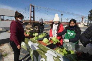Una larga cola de gente que fue a recibir verduras regaladas