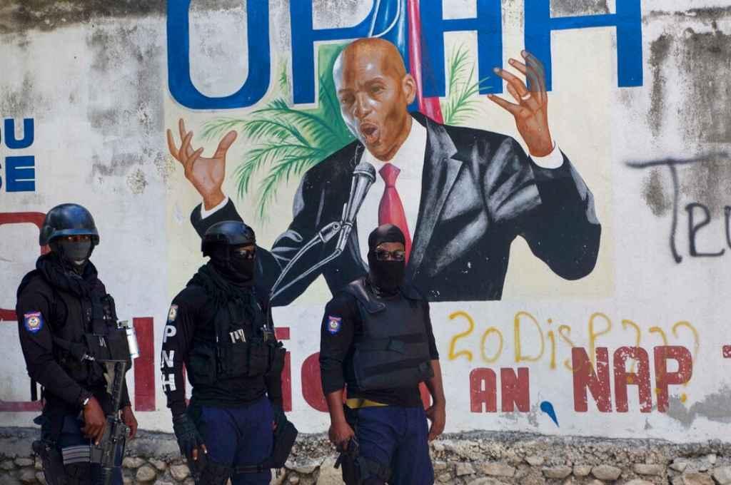 La policía haitiana frente a un mural con imagen del presidente haitiano asesinado, Jovenel Moïse.    Crédito: Gentileza