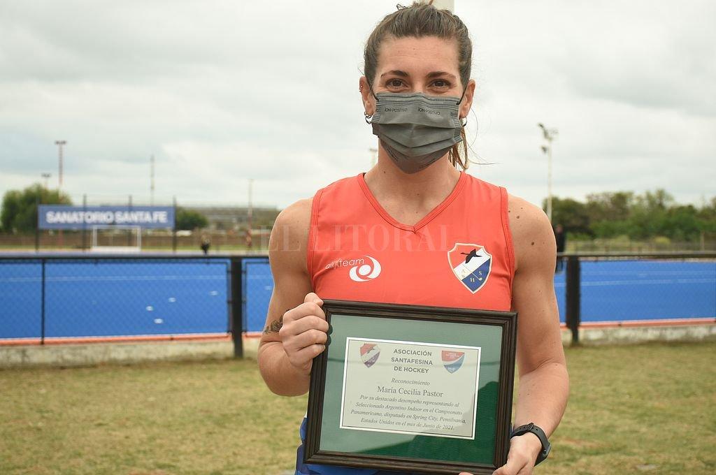 Plaqueta de reconocimiento en mano para María Cecilia Pastor, que en junio fue medalla de bronce con el seleccionado argentino en el Panamericano de Pista. Crédito: Manuel Fabatia