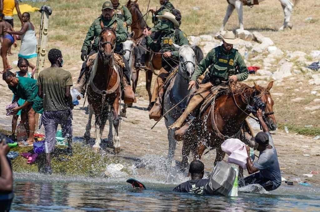 El servicio de vigilancia fronteriza de Texas utiliza sus riendas a modo de látigo contra los inmigrantes haitianos ilegales que intentan refugiarse en Estados Unidos.    Crédito: Gentileza