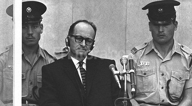 Eichmann, flanqueado por policías israelíes, asiste dentro de un cubículo de seguridad, al desarrollo de su juicio por el exterminio de judíos en la ciudad de Jerusalén. Crédito: Archivo El Litoral